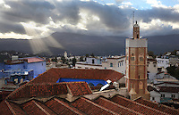 The Grande Mosquee or El Masjid El Aadam with its octagonal minaret, in Chefchaouen in the Rif mountains of North West Morocco. The mosque was built adjoining the kasbah by the son of the town's founder, Ali Ben Rashid. It has longitudinal naves, a prayer hall with 4 gates, a terracotta tiled roof and an octagonal minaret typical of the region. Chefchaouen was founded in 1471 by Moulay Ali Ben Moussa Ben Rashid El Alami to house the muslims expelled from Andalusia. It is famous for its blue painted houses, originated by the Jewish community, and is listed by UNESCO under the Intangible Cultural Heritage of Humanity. Picture by Manuel Cohen