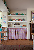 Crockery is displayed on open shelving in the kitchen while a curtain conceals further storage