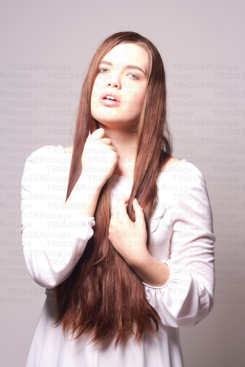 A portrait of a young pale woman with long brunette hair