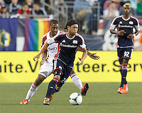 New England Revolution midfielder Lee Nguyen (24) dribbles as Toronto FC midfielder Reggie Lambe (19) defends. In a Major League Soccer (MLS) match, Toronto FC (white/red) defeated the New England Revolution (blue), 1-0, at Gillette Stadium on August 4, 2013.