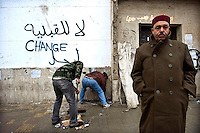 Residents of Benghazi sweeping the streets after days of fighting between pro and anti government forces in Benghazi. A wall shows a graffiti in Arabic and English which reads: 'Change'. The eastern city of Benghazi, birthplace and stronghold of the revolution against the regime of Muammar Gaddafi, was taken by rebel forces after heavy fighting with forces loyal to the regime. ....foto: Sven Torfinn. Libya, Benghazi, Februari 2011. Bewoners van Benghazi hebben zich georganiseerd. 13 comitees zijn aangesteld om er voor te zorgen dat zaken als stroom, water, reiniging, gezondheidszorg blijven funcitoneren nu Benghazi niet meer onder het gezag van de regering Khaddafi valt. Teams van vrijwilligers vegen de straten schoon.
