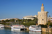 General view of Torre del Oro (Tower of Gold) and River Guadalquivir, Seville, Spain, pictured on December 30, 2006, in the afternoon. The tower, first half of the 13th, century, is dodecagonal in shape and divided into three levels. The circular top level was added in 1760. It served as an observation post at the entrance to the port on the Guadalquivir River during the conquest of Americas. Today it houses the city's Naval Museum. The modern, round building to the left of the Torre del Oro is the 1800 seat Teatro Maestranza, built for the 1992 Expo. Home to the Royal Seville Symphony Orchestra, this hosts internationally-renowned performances of opera, ballet and music. Pleasure boats are moored on the river next to the Tower. Picture by Manuel Cohen.