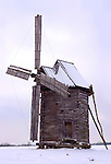 Ancient log windmill in a snow covered field Ukraine Eastern Europe Countryside winter scenic Vertical orientation