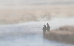 Two people fish on the Madison River in yellowstone National Park on a foggy morning in October.