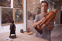 Gallery employee arranges a sculpture depicting Soviet leader Vladimir Ilyich Lenin. Large number of artifacts from Hungary's socialist past found in the basements of different ministries after a change in political power. These communist pictures and sculptures are now being prepared for a charity auction to support those affected by the recent red sludge catastrophe in Hungary. The auction drawing great attention from around the world is to be held on December 6th in Budapest, Hungary. Photos taken during preparations for the auction on November 25, 2010. ATTILA VOLGYI