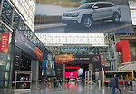 Manhattan, New York, USA. April 12, 2017. In vast interior of Javits Center, visitors approach Entrance to New York International Auto Show 2017. Above NYIAS entrance is huge banner for Volkswagon, and through entrance is Nissan display.
