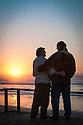 Gay couple at sunset on deck of beach house at Yachats on the central Oregon coast.