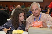 OrigamiUSA 2014. Koustubh Oka (right) teaches Kika Salgo how to fold an origami model between classes.
