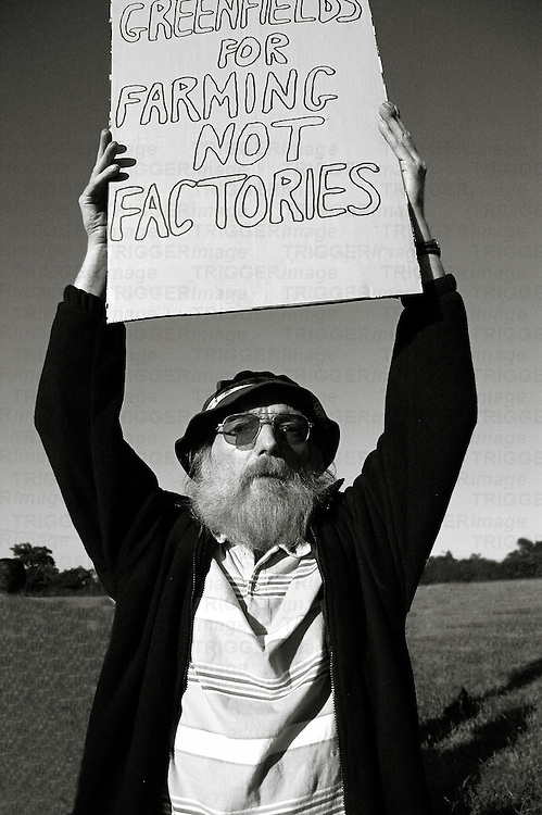 An old man with a beard protesting about factories on farmland