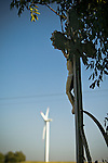 A cross stands under a tree and in the background a windmill turns in the breeze. Eastern Czech Republic.