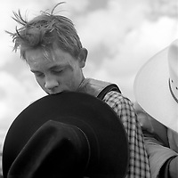 A 14-year-old saddle bronc rider named Tony pauses for a prayer at the start of the Earl Anderson Memorial Rodeo in Grover, Colo. Tony carries the scars of a committed rider.