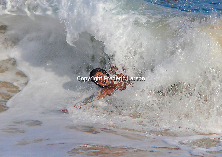 A woman blast through a wave at Sandy Beach in Hawaii during high-tide.