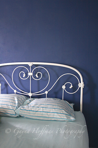 White iron bed against blue wall.