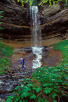 A WOMAN MAKES HER WAY ALONG THE ROCKS BELOW MUNISING FALLS IN PICTURED ROCKS NATIONAL LAKESHORE IN MUNISING, MICHIGAN.