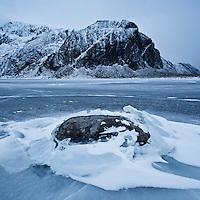 Rock emerges from ice on frozen lake Nedre Heimdalsvatnet, Eggum, Lofoten Islands, Norway