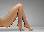 Woman legs in beige fishnet pantyhose isolated on gray studio background