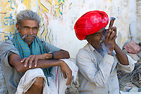 Indian man in traditional clothing smokes clay pipe while sitting with a friend in Narlai village in Rajasthan, Northern India