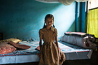 India - West Bengal - Dooars Region - Kumari, 9, sits on her aunt's bed at her family home in Mogulkata Tea Estate. Kumari's family has been living in the Tea Estate for 3 generations and she will probably be taking her mother or father's position once they will retire in order to avoid being kicked out of their land and considering the very little job opportunities in a very isolated village. <br /> <br /> India is the second largest tea producer in the world. But while its green leaves are on the shelves of every supermarket and tea boutique across the globe, women workers still live under the remnants of a slavery system conceived under British colonialism.<br /> <br /> Tea is one of the biggest industries in India, accounting for 14 percent of world tea exports and employing 3,5 million people, the vast majority of them women. Here, managers still roam on horses, dressed in sleek shirts and shorts in homage to old British custom. Yet, just few hundred meters away from their leafy offices, more than 2,000 tea workers have died of malnutrition in the past 15 years, while scores of others have ended up working as stonecrushers, maids or prostitutes in a vain attempt to escape misery.<br /> <br /> Uprooted from their ancestral lands and now hosted in isolated, rundown colonies lost amid the plantations, women pluckers earn less than two dollars per day, half the minimum wage set by the government. With their housing, healthcare, education and pension conditional to their lifetime staying in the garden, they have no properties and cannot emigrate, change job or break the chains which have kept them bonded for generations. In the frequent case of tea garden closures, their wages, water supplies and food rations are cut overnight, leaving them with no choice but to starve.