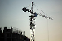 Construction workers work on a building next to a crane in Ufa, Bashkortostan, Russia.
