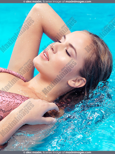 Closeup of beautiful young woman face with closed eyes in blue water
