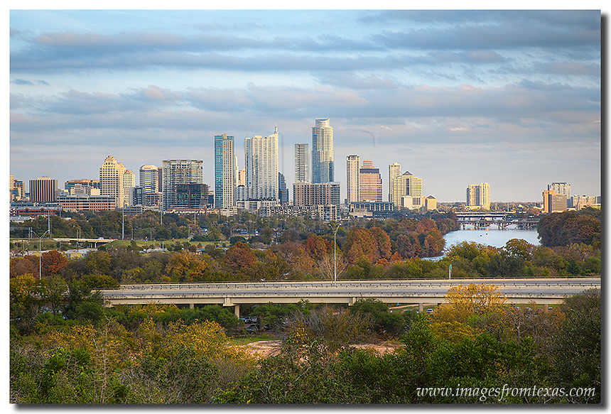From the balcony at the Zilker Park Clubhouse, the fall colors that surround Lady Bird Lake and Zilker Park offer a beautiful scene for viewing or taking a stroll. In the distance, the Austin skyline rises from the basin with the Austonian and the Frost Bank Tower, and Austin icon, the most prominent buildings. This Austin image was captured in late November on a nice cool evening.