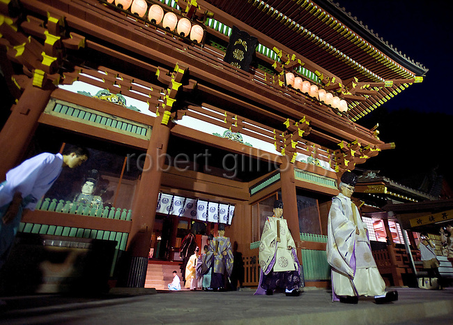 """Head priest Shigeho Yoshida leads a procession out of the gate of the """"Hongu"""" main shrine following a ritual during which a variety of  goods are  offered to the gods  to announce the start of the annual 3-day Reitaisai grand festival at Tsurugaoka Hachimangu shrine in Kamakura, Japan on  14 Sept. 2012.  Photographer: Robert Gilhooly"""