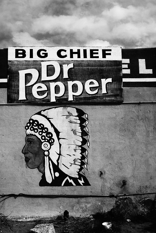 a native american profile painted on the side of an adobe building with a dr. pepper sign make interesting contrasts regarding native american culture and european american culture, big chief gas station, san ysidro, new mexico