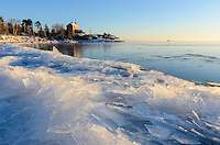 A winter view of the Marquette Harbor Light, on Lake Superior, with fresh layers of ice shards piled along the shoreline. Marquette, MI