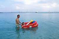 """Spain. Mallorca in the Balearic islands. Colonia Sant Jordi. A father and his daughter play with a inflatable boat """" fire boat"""" in the mediterranean sea. © 1999 Didier Ruef"""