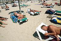 "Spain. Mallorca in the Balearic islands. Palma. Tourists take a rest, sunbathe and sleep on plastic chairs in the sandy beach of "" Playa de Palma"". © 1999 Didier Ruef"