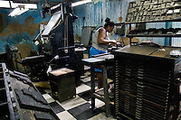 A Cuban woman setting letters and words into a printing block in the type section of the state print shop in Santiago de Cuba, Cuba, 4 August 2008.