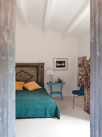 View into the bedroom furnished with a mix of styles with a rustic wooden headboard and blue retro sidetable