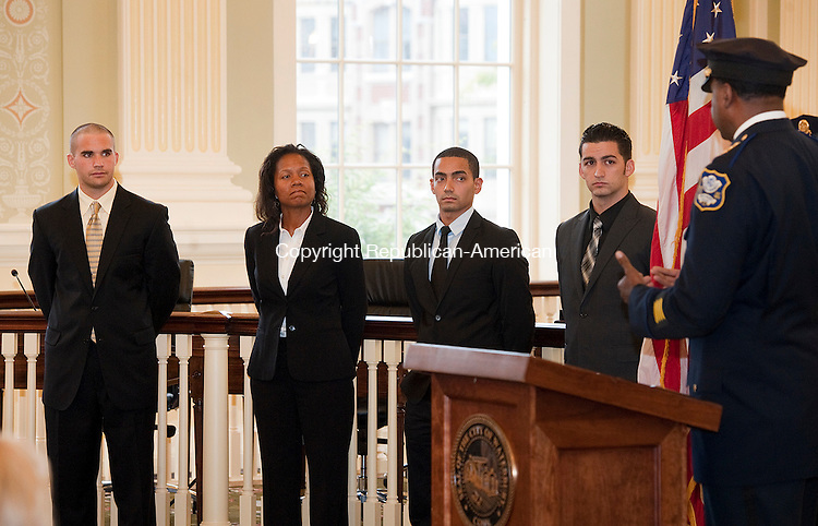 WATERBURY, CT--- -100115JS01---Waterbury's newest police officers, from left, Philip V. Miccio; Judith E. Morisset; Nathaniel E. Hernandez and Joseph M. Polaco, listen as Waterbury Police Chief Vernon L . Riddick Jr. right,  talks about pride, personal responsibility and integrity during swearing in a ceremony Thursday in the Aldermanic Chambers in City Hall on Thursday. The offers were sworn in by Waterbury Mayor Neil M. O'Leary. <br /> Jim Shannon Republican-American