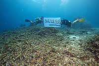 Greenpeace activists show their message at the destroyed reef of the MPA at Apo Island.