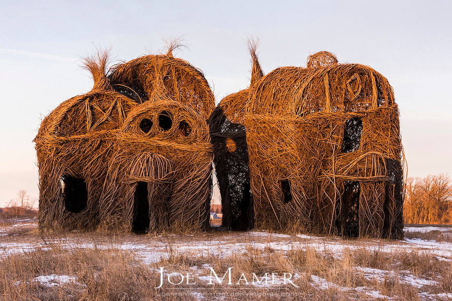 """Environmental artist Patrick Dougherty took up residence at the College of Saint Benedict / Saint John's University in September of 2012. During his time in the St. Cloud are he erected a large-scale outdoor sculpture made of sustainably harvested saplings from Saint JohnÕs Arboretum. The structure, called Lean On Me, consists of five small """"chapels"""" huddled next to each other."""