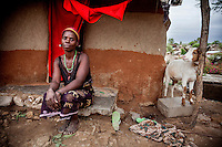 Witchdoctor Pasqua Mutundu with her goat outside her 'hospital' hut.