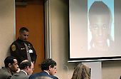 Sniper suspect John Allen Muhammad, left, and his defense attorneys Peter Greenspun, seated center, and Jonathan Shapiro, right of Muhammad, listen to court proceedings as a photo of fellow sniper suspect Lee Boyd Malvo is displayed on a screen during the Muhammad trial at the Virginia Beach Circuit Court  in Virginia Beach, Virginia on October 24, 2003.  The photo of Lee Boyd Malvo was used since Malvo was not available in court. <br /> Credit: Davis Turner - Pool via CNP