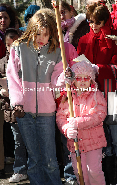 (Left) Grace Weldon and Caitlyn Mitchell were a couple of volunteers who carried a spear with dozens of Good Friday observers who gathered to celebrate the Way of the Cross service at Shrine of Lourdes in Litchfield Friday morning. Stations depicting the crucifixion and resurrection of Jesus are positioned along a paved path in the woods on the Shrine's grounds. . Michael Kabelka / Republican-American