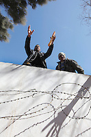 Refugees try to get bread and other suplies that are thrown to them over the border wall. Tens of thousands of people, mainly Egyptian workers, fled unrest in Libya and crossed the border into Tunisia. Some slept in the open for several days before being processed.  At the same time forces loyal to Col. Gaddafi fought opposition forces in various parts of the country.