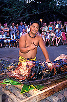 """A Hawaiian man dressed in a traditional  garment, makes a """"""""shaka"""""""" sign while standing over a roasted kalua pig at the Kona Village Resort. Seated tourists watch the ceremony."""