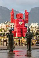 "South Africa, Cape Town.  Nobel Square Statues of Desmond Tutu and FW de Klerk. Sculptor Claudette Schreuders.  In background is the ""Lego Man"" sculpture made of 4200 plastic  Coca Cola crates.  Designed by Porky Hefer."