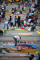 "Contest participants busy themselves creating ""rugs"" made of flowers on the procession route Wednesday in Ayacucho, Peru."