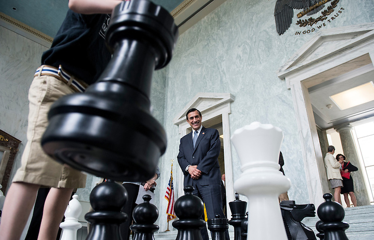 "UNITED STATES - MAY 7: Rep. Darrell Issa, R-Calif. watches kids move giant chess pieces in the Rayburn Foyer during the ""Chess Challenge on the Hill"" on Wednesday, May 7, 2014. Issa and Del. Eleanor Holmes Norton, D-D.C., hosted the event to ""to showcase chess as a way to promote the academic, social, and leadership development of youth, and highlight the work being done with elementary and middle schoolchildren in the District of Columbia by the nonprofit group Chess Challenge in D.C."" (Photo By Bill Clark/CQ Roll Call)"