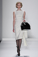 Model walks runway in an ivory wool boucle sheath dress seamed w/mink-chain, from the Zang Toi Fall 2012 &quot;Glamour At Gstaad&quot; collection, during Mercedes-Benz Fashion Week New York Fall 2012 at Lincoln Center.