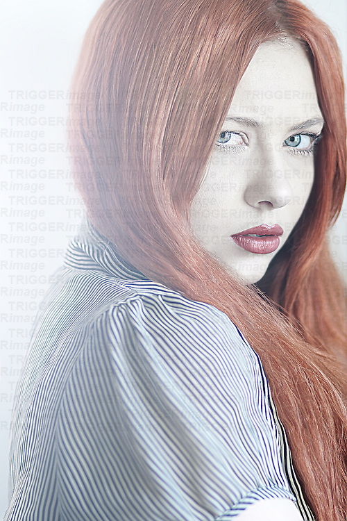 Female youth with long red hair looking at camera