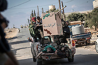 In this Thursday, Sep. 19, 2013 photo, two dead bodies of soldiers loyal to president Bashar Al-Assad are carrying out at the back of a truck after were removed from the battlefield in the neighbouring village of Kafr Nabuda in the Idlib province countryside, Syria. (Photo/AP).