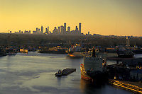 Tankers docked in the Port of Houston in front of the skyline at sunset