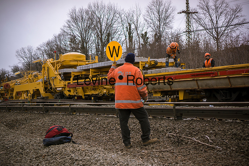 Long Island Railroad workers, using Hasco Track Replacement System machinery on Thursday, March 21, 2013, replace track damaged by a derailment of an empty train earlier in the week. Sixteen hundred concrete ties have been replaced by the machine over the three-quarters of a mile of damaged track. Over the weekend crews will replace the 3700 feet of third rail with service hopefully being restored by the Monday morning rush hour.  (© Richard B. Levine)