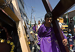 A Nazareno carries a wood cross as he makes his way to the top of Iztapalapa hill where Jesus Christ will be hanged on a cross, April 14, 2006. Almost a million people attend the procession of Good Friday in this  neighborhood of Mexico City, where for 163 years the Iztapalapa neighborhood residents have taken part in a re-enactment of Christ's crucifixion.  Photo by © Javier Rodriguez