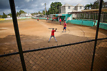 Coach Hector Ramirez hits ground balls during infield practice for the Warriors baseball team at the municipal stadium on Thursday, February 25, 2010 in San Antonio de Guerra, Dominican Republic.